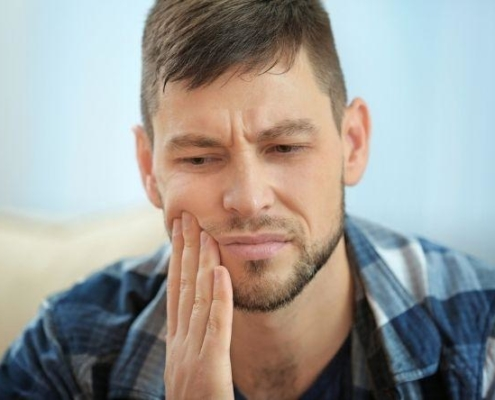 a man holding the side of his mouth because he is experiencing tooth sensitivity